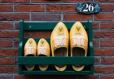 Storage rack with clogs next to frontdoor. Storage rack with wooden shoes next to Dutch frontdoor Stock Photos