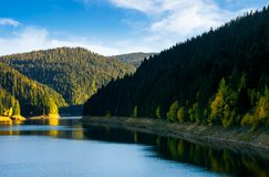 Storage reservoir in mountain at sunrise. Beautiful landscape in early autumn stock photography