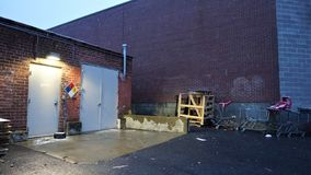 Storage shed entrance for hazardous materials. Loading dock behind brick lined box store has posted warnings of stored chemicals. Harsh illumination lights rat royalty free stock photo