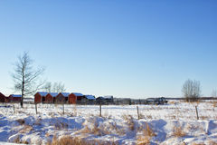 Storage sheds and corral in the winter. A landscape of sheds and two trees in the countryside on snow covered ground Stock Image