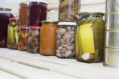Storage shelves in pantry with homemade canned preserved fruits and vegetables.  Royalty Free Stock Image
