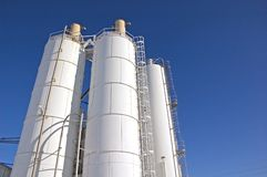 Storage Silos. Photograph of a series of 3 storage silos silhouetted against a blue sky Royalty Free Stock Image