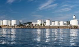 Storage silos,fuel depot of petroleum and gasoline on the banks of the river in western Germany on a beautiful blue sky with cloud royalty free stock photo