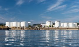 Storage silos,fuel depot of petroleum and gasoline on the banks of the river in western Germany on a beautiful blue sky with cloud stock image