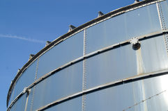 Storage tank. Rusty industrial storage tank with a valve against blue sky Royalty Free Stock Photo