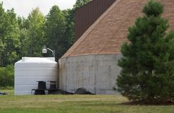 Storage tank beside building Stock Image