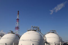 Storage tank chemical industry. Petrochemicals with smoke and blue sky background Stock Photo