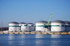 Storage tanks in the harbour 2. Oil terminal with storage tanks and green port crane in the harbour Royalty Free Stock Photography