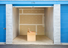 Storage: Woman Closing Box in Storage Unit. Caucasian man and woman with various props at a typical commercial storage unit Stock Images
