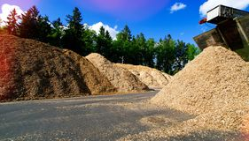 Storage of wooden fuel biomass against blue sky. And forest royalty free stock photos