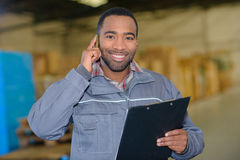 Storage worker on phone Stock Images