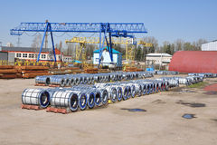 The storage yard for steel. Shear legs cranes at the storage yard with polymer rolls, steel sheets in packs and tubes in packs Royalty Free Stock Images
