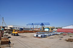 The storage yard for steel. Shear legs cranes at the storage yard with polymer rolls, steel sheets in packs and tubes in packs. The truck in on loading Royalty Free Stock Photos