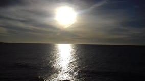 Storartad enorm sol som skiner ner på det stillsamma havet Fotografering för Bildbyråer