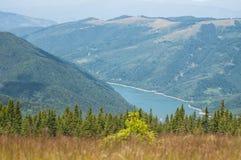 Storartad sikt av berg som täckas av skogar och en sjö på Poiana Marului Royaltyfri Foto