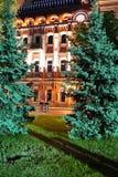 Storartad sikt från en grön gräsmatta med placerade träd på ett hotell med härlig arkitektur som är upplyst vid afton Fotografering för Bildbyråer