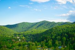 Storartade gröna kullar och skog med olika träd mot den blåa himlen En liten tältstad i djupen av taigaen royaltyfri fotografi