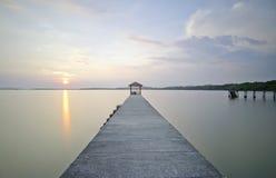 Storartade solnedgång- och sjöreflexioner på den långa bryggan Arkivbild