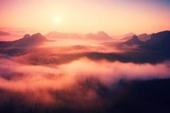 Storartat bergigt landskap i försiktig rosa rosa soluppgång Den härliga dalen av steniga berg parkerar Kullar ökande från morgone arkivbilder