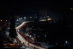 Storartat nattlandskap av den ukrainska byn i ljust ljus och suddiga billjus royaltyfri fotografi