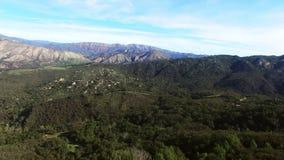Storartat skott av parkeringsplatsen med turister och dalen med kullar och skogar stock video