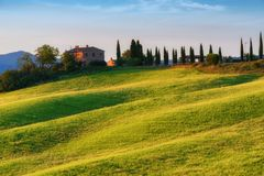 Storartat vårlandskap på soluppgång Härlig sikt av det typiska tuscan lantgårdhuset, kullar för grön våg royaltyfria bilder