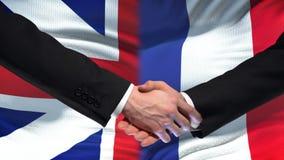 Storbritannien och Frankrike handskakning, internationellt kamratskap, flaggabakgrund lager videofilmer