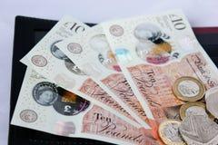 Storbritannien pund och encentmynt i öppen handväska på vit bakgrund royaltyfria foton