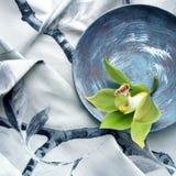 Storczykowy kwiatu set przeciw popielatej drukowanej tkaninie Zdjęcie Stock