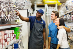 Store assistant helping customers. Friendly african hardware store assistant helping young couple choosing taps stock images