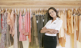 Store Assitant Standing by Hanging Clothes in Store Royalty Free Stock Images