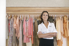 Store Assitant Standing by Hanging Clothes in Store Stock Photos