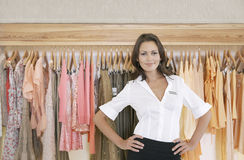 Store Assitant Standing by Hanging Clothes in Store Royalty Free Stock Photography