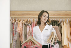 Store Assitant Working and Hanging Clothes in Store Royalty Free Stock Images