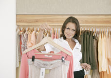 Store Assitant Working and Hanging Clothes in Store Royalty Free Stock Image