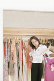 Store Assitant Working and Hanging Clothes in Store stock images