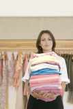 Store Attendant Holding Pile of Clothes Stock Photo