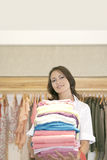 Store Attendant Holding Pile of Clothes Royalty Free Stock Photo