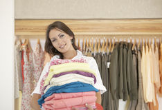 Store Attendant Holding Pile of Clothes. Shop assistant holding a pile of clothes in a fashion store Royalty Free Stock Photos