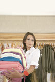 Store Attendant Holding Pile of Clothes Stock Photos