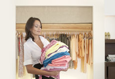 Store Attendant Holding Pile of Clothes Stock Photography