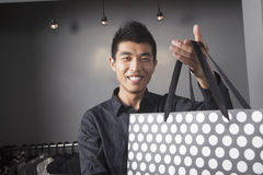 Store clerk holding shopping bag at fashion store Stock Image