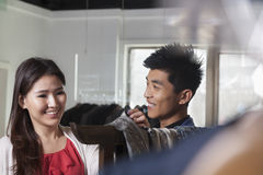 Store clerk showing scarfs to young woman at fashion store Stock Images