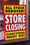 Store closing poster. In a window of a bankrupt shop advertising all stock reduced Royalty Free Stock Photo