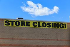Store Closing Sign. A large store closing banner sign attached to a wall stock photo