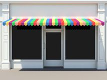 Store with colored awnings. Shopfront in the sun - classic store front with colored awnings Stock Image