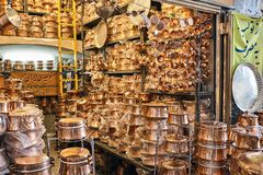Shelves in a store of copper utensils at the market. A store of copper and brass cookware in the Iranian town of Yazd, shelves with metal utensils Royalty Free Stock Photography