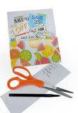 Store Coupons. A coupon book with shopping list , pen & scissors royalty free stock photo