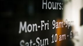 Store hours in white writing on store window royalty free stock photography