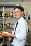 Store keeper. At work holding wine smiling royalty free stock photo